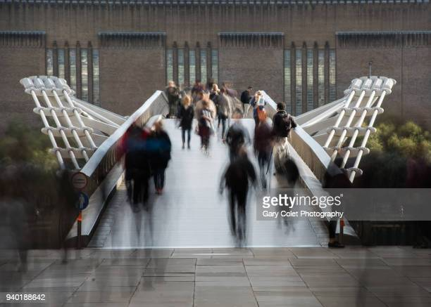 long exposure of walkers on millennium bridge, london - gary colet stock pictures, royalty-free photos & images