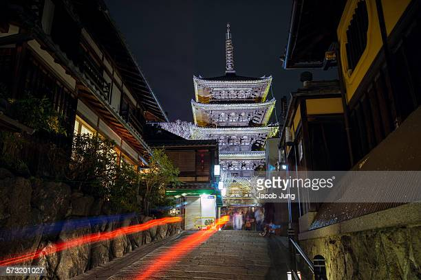 Long exposure of Yasaka Pagoda with light trails from a taxi in the foreground during the Hanatoro lantern illumination event in Kyoto's Higashiyama...