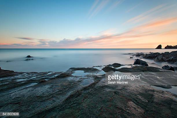 long exposure on a rocky beach at sunset - cap d'agde stock photos and pictures