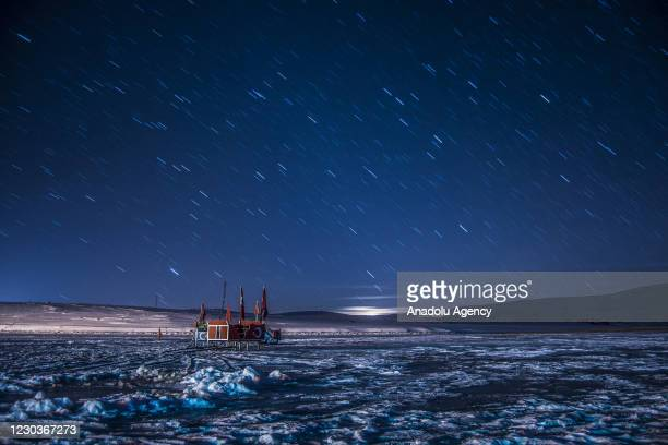 Long exposure photo shows stars in the night sky over the Lake Cildir, where parts of its surface are frozen in Kars, Turkey on December 30, 2020.
