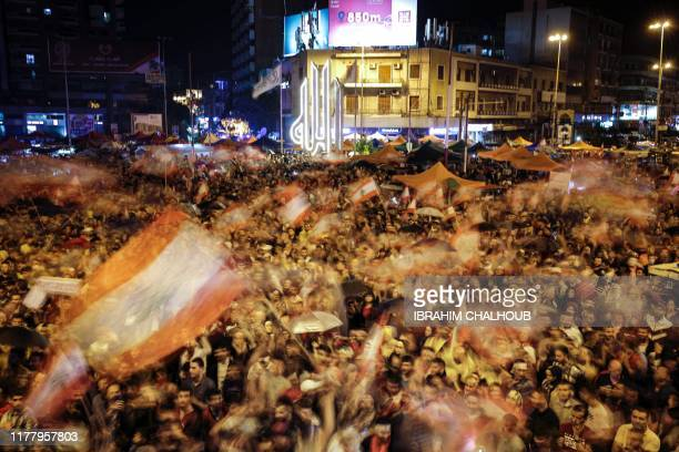 A long exposure photo taken on October 24 depicts Lebanese protesters waving national flags at alNour Square in Lebanon's northern city of Tripoli on...