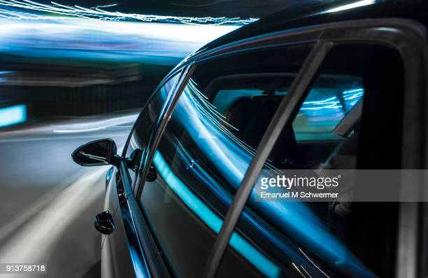 Long exposure photograph of a black German car driving on Mallorca, left windows with reflections in foreground, rear view mirror in middle ground and motion blurred background.