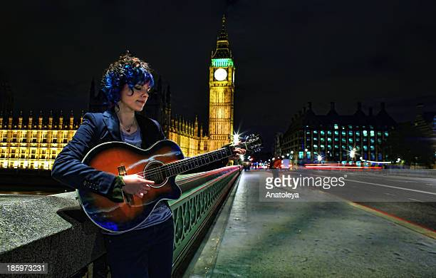 Long exposure photograph of a busker playing the guitar on Westminster Bridge, London, at night.