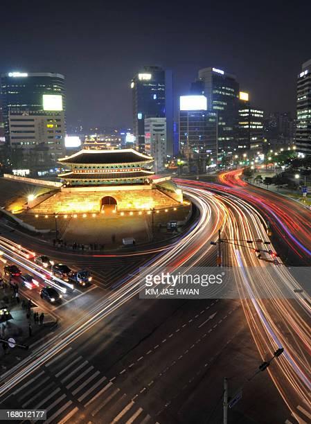 A long exposure photograph shows traffic commuting at night near South Korea's landmark Namdaemun gate in Seoul on May 4 2013 South Korea on May 4...