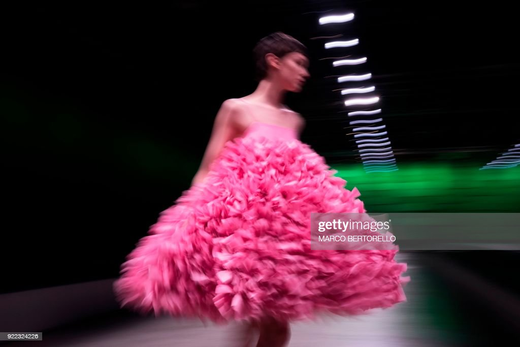 TOPSHOT - A long exposure picture shows a model presenting a creation by Annakiki during the women's Fall/Winter 2018/2019 collection fashion show in Milan, on February 21, 2018. / AFP PHOTO / Marco BERTORELLO
