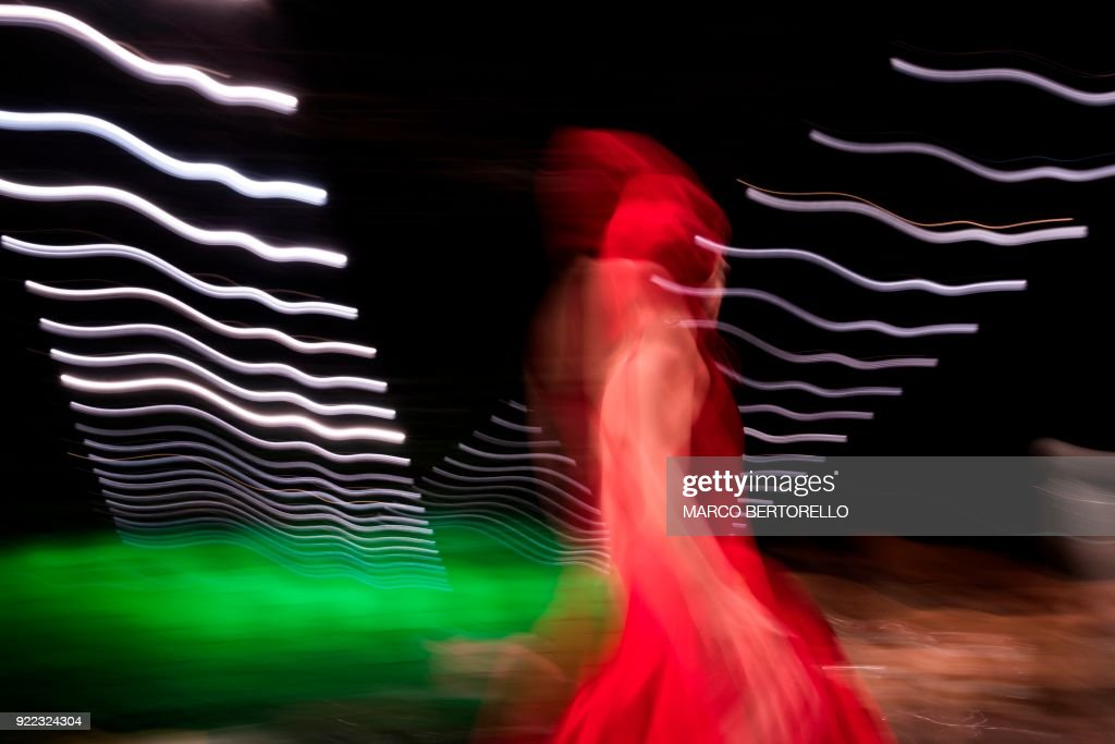 A long exposure picture shows a model presenting a creation by Annakiki during the women's Fall/Winter 2018/2019 collection fashion show in Milan, on February 21, 2018. / AFP PHOTO / Marco BERTORELLO