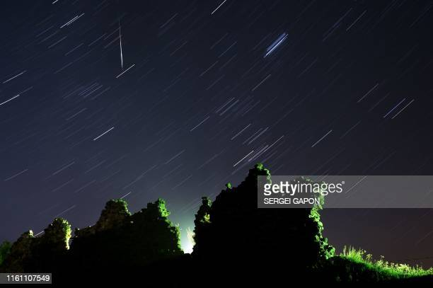 A long exposure picture shows a Perseid meteor crossing the night sky and stars trails above the ruins of a medieval castle in the village of Kreva...