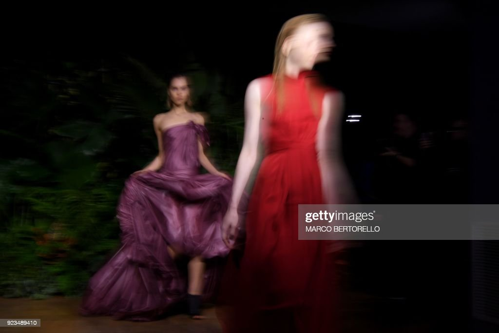 A long exposure picture shows models presenting creations by Vionnet during the women's Fall/Winter 2018/2019 collection fashion show by Vionnet, in Milan, on February 23, 2018. / AFP PHOTO / Marco BERTORELLO