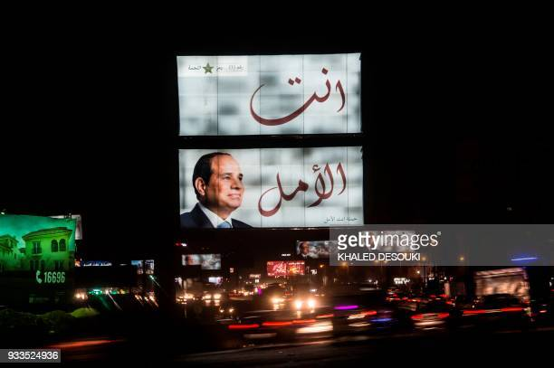 TOPSHOT A long exposure picture taken on late night of March 17 shows a giant election campaign board supporting Egyptian President Abdel Fattah...