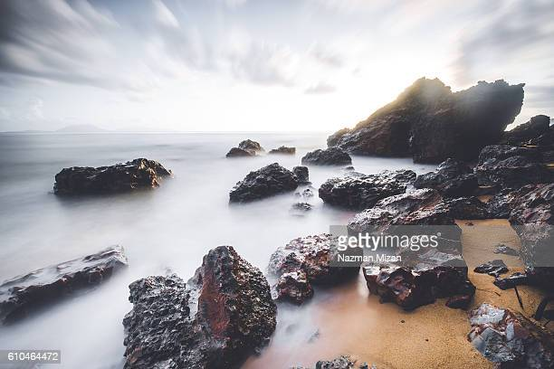 Long exposure shot of a seascape with beautiful rocks in the foreground.