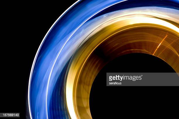 long exposure shot of blue and yellow spinning lights - gold circle stock pictures, royalty-free photos & images
