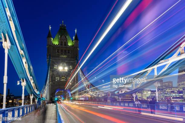 long exposure shot of the tower bridge with a london's iconic red bus. - london bridge stock pictures, royalty-free photos & images