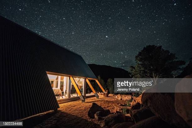 long exposure side-angle photo of a modern a-frame tiny home glowing at night with millions of bright stars on a clear night in the summer - national forest stock pictures, royalty-free photos & images