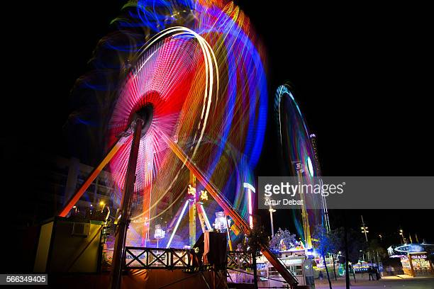 Long exposure view of a colorful fun fair attractions at night with people having fun on saturday night