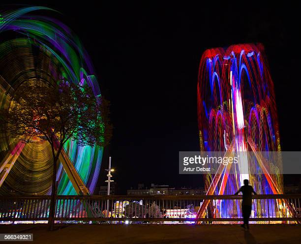 Long exposure view of a two ferris wheel in a fun fair with people on summer night