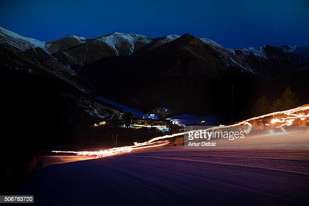 Long exposure view of skiers descending the ski resort at night with fire torches in the Pyrenees mountains.