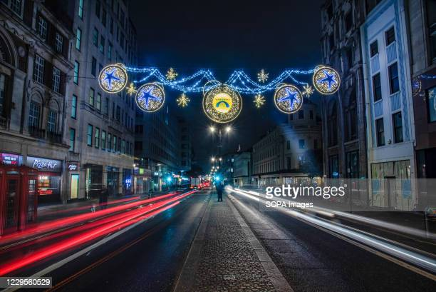 Long exposure view of traffic driving underneath the Christmas Lights on The Strand in London.