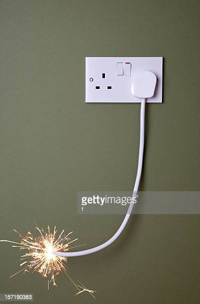 long fuse burning towards plug socket. - fuse stock photos and pictures