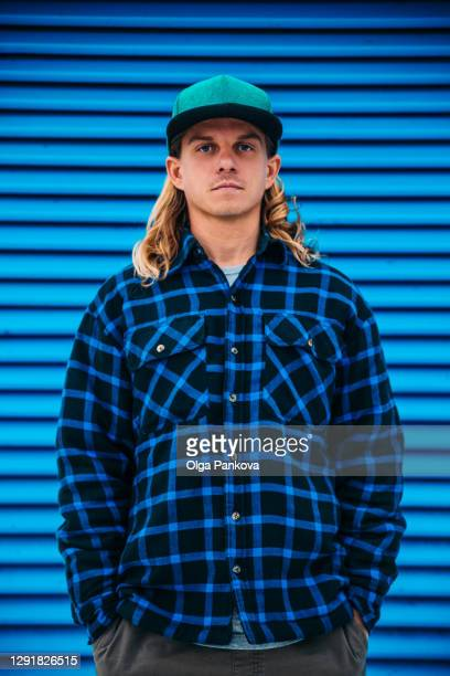 a long hair man in a green cap and a blue plaid jacket against a blue wall. - portrait blue background stock pictures, royalty-free photos & images