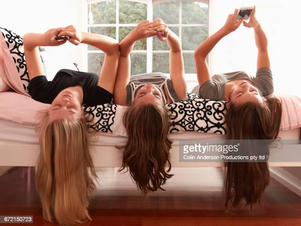 Long hair of Caucasian girls using cell phones hanging from bed