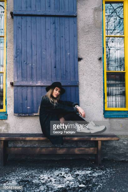 long haired blond woman wearing a black fedora hat, a black coat with woollen lapels, and white boots, sitting on a wooden bench behind blue window shutters - black boot stock pictures, royalty-free photos & images