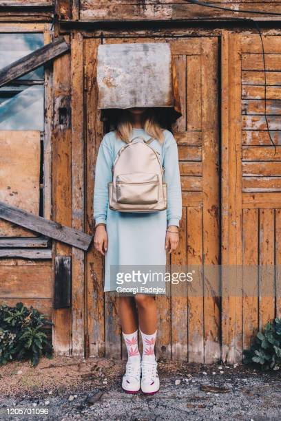 a long haired blonde woman, wearing a powder blue dress, white socks with pink marijuana motifs, white trainers and a pink backpack the wrong way round, wearing on her head a rusty metal container. fashion creative concept. - fashion collection stock pictures, royalty-free photos & images