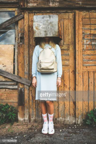 a long haired blonde woman, wearing a powder blue dress, white socks with pink marijuana motifs, white trainers and a pink backpack the wrong way round, wearing on her head a rusty metal container. - dress over pants stock pictures, royalty-free photos & images