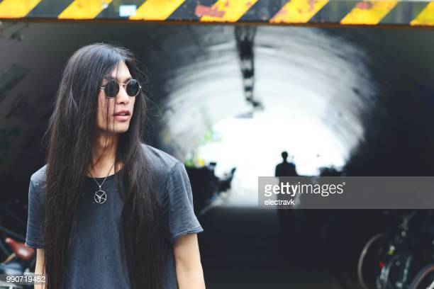 long haired man standing in front of tunnel - somente japonês - fotografias e filmes do acervo