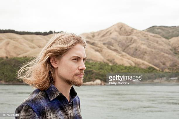 long haired man staring out to sea pensively - mittellanges haar stock-fotos und bilder