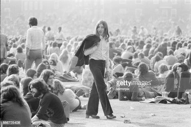 Long haired music fan, jack over his shoulder, wanders through the huge crowd and audience enjoying The Oval Pop Festival, Oval Cricket Ground, South...