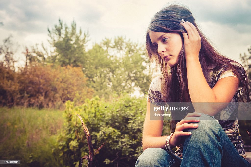 Long Haired Teen Girl Sitting Alone Outdoors With Sad Expression Stock Photo