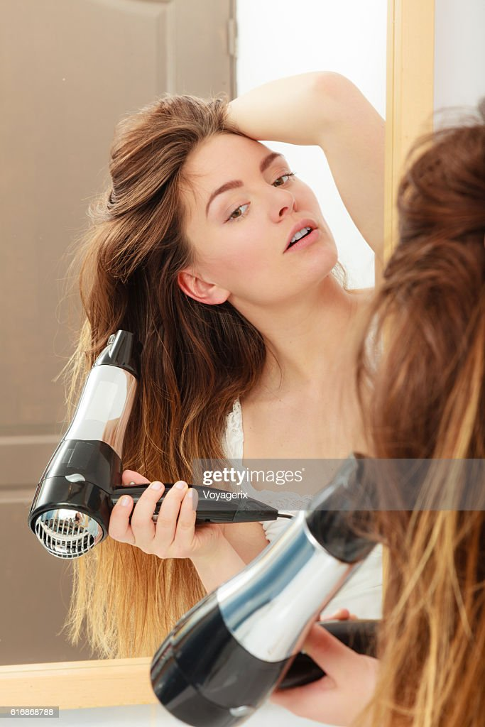long haired woman drying hair in bathroom : Stock Photo