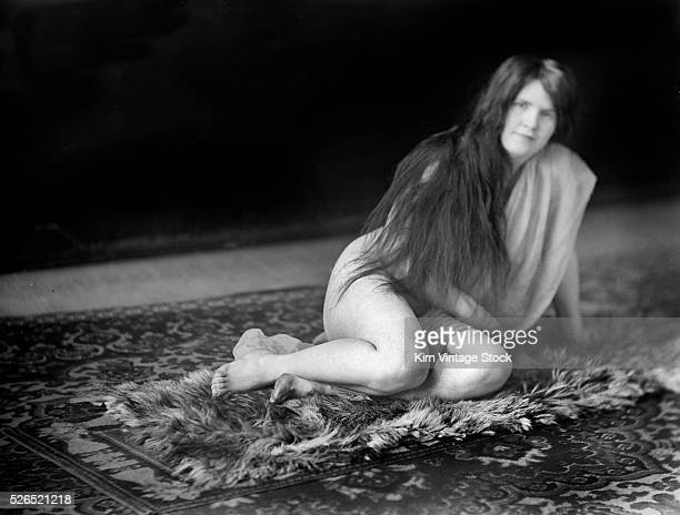 A long haired woman in semiclothed state sprawls on a rug for a portrait
