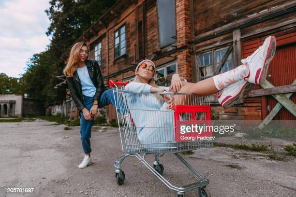 a long haired woman wearing a powder blue dress, pink woollen hat is chilling with her female friend, who is sitting on a shopping trolley, wearing a black leather jacket and blue jeans, in a derelict trading estate - love magazine stock pictures, royalty-free photos & images