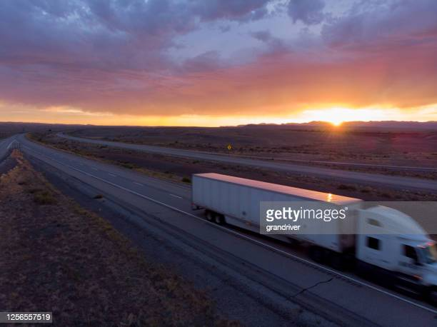 long haul freight hauler semi-truck and trailer traveling on a four-lane highway in a desolate desert at dusk or dawn - refrigerator truck stock pictures, royalty-free photos & images