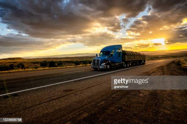 long haul semi truck speeding down a four lane highway in a beautiful sunset - trucking stock pictures, royalty-free photos & images