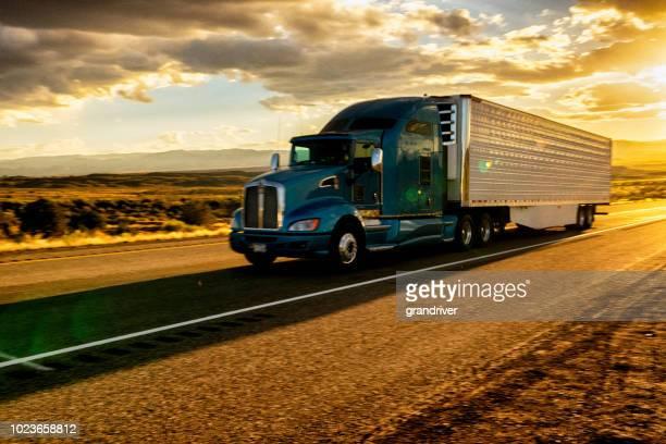 camiones larga distancia exceso de velocidad por una autopista de cuatro carriles en una hermosa puesta de sol - camión articulado fotografías e imágenes de stock