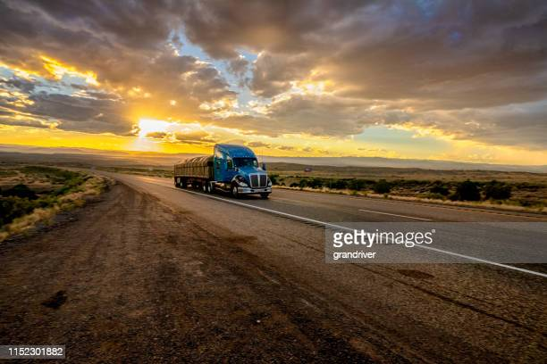 long haul semi truck speeding down a four lane highway in a beautiful sunset - convoy stock pictures, royalty-free photos & images