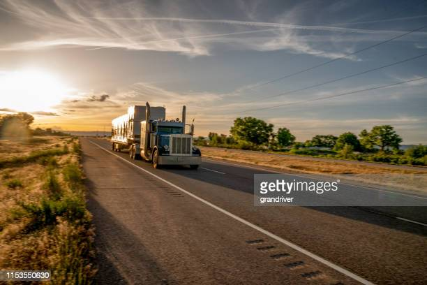 long haul semi truck speeding down a four lane highway in a beautiful sunset - semi truck stock pictures, royalty-free photos & images