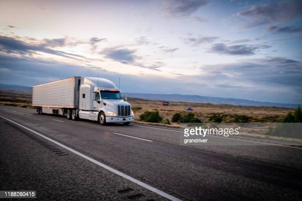 long haul semi trucks speeding down a four lane highway to delivery their loads - major road stock pictures, royalty-free photos & images