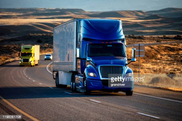 long haul semi-truck rolling down a four-lane highway at dusk - convoy stock pictures, royalty-free photos & images
