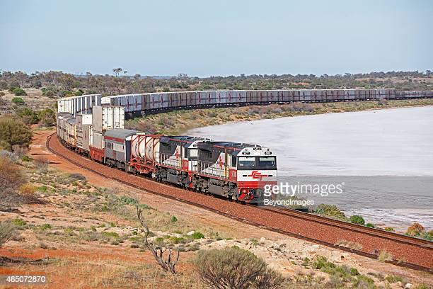 Long high-capacity SCT freight train passing dry salt lake