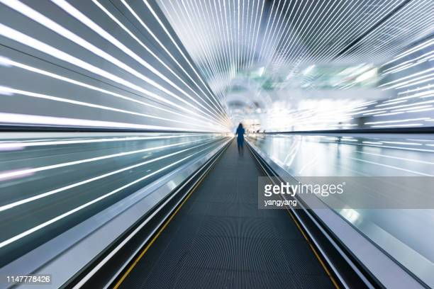 long horizontal escalator at international airport terminal - vision stock-fotos und bilder