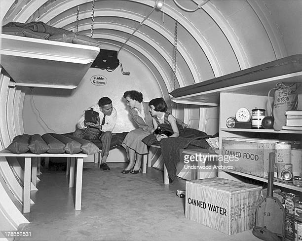 A Long Island family sits in a 'Kidde Kokoon' an underground bomb shelter manufactured by Walter Kidde Nuclear Laboratories Garden City New York 1955