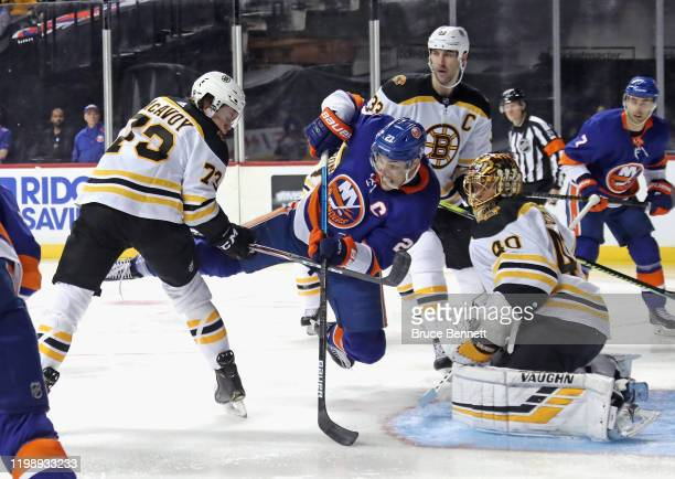 Long Island native Charlie McAvoy of the Boston Bruins trips up Anders Lee of the New York Islanders during the second period at the Barclays Center...
