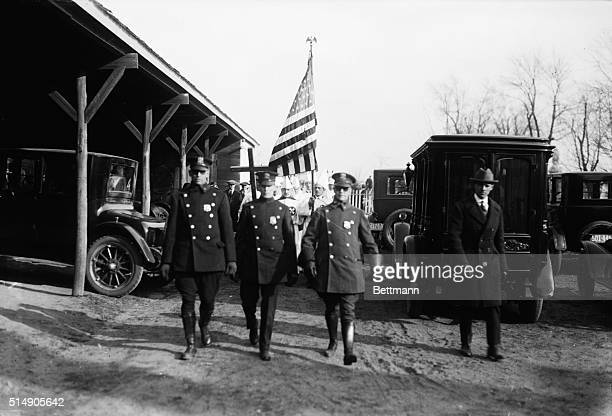 A Ku Klux Klan funeral procession protected by policemen Freeport LI Undated photograph