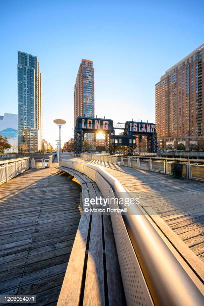 long island pier and skyscrapers at sunrise, new york city - queens stock-fotos und bilder