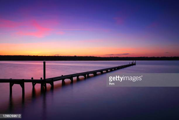 long jetty at sunset - jetty stock pictures, royalty-free photos & images