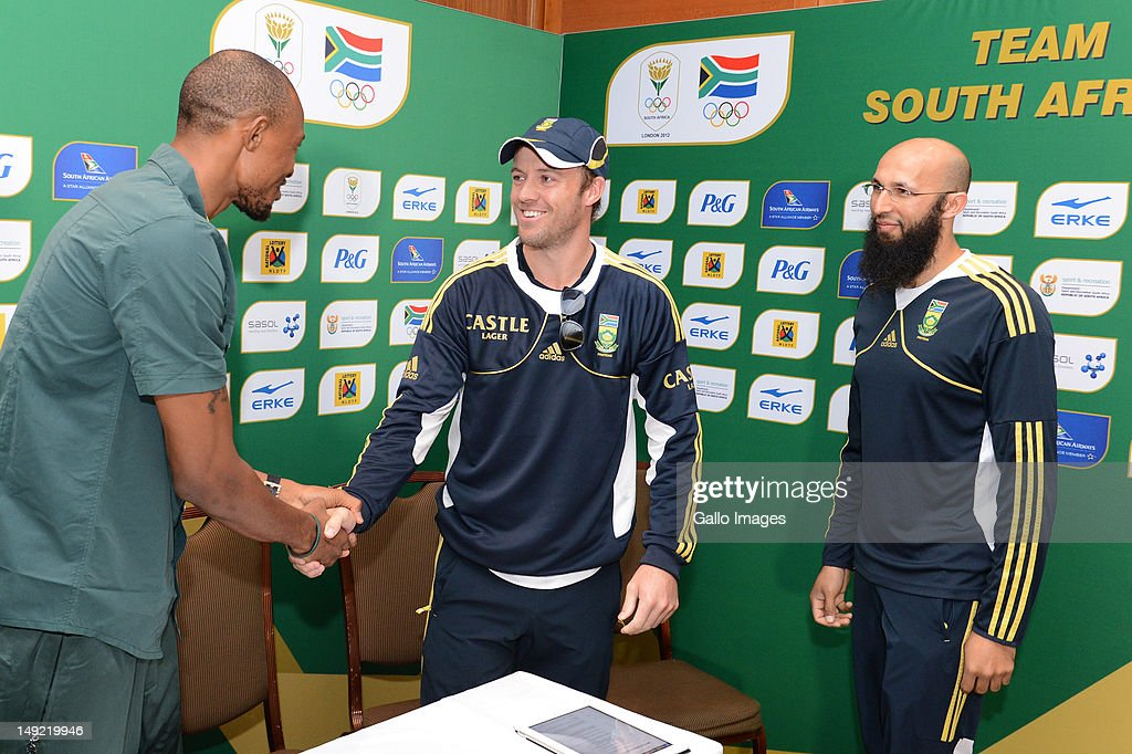 Long jumper Khotso Mokoena is greeted by AB De Villiers and Hashim Amla, Protea's cricketers, during the South African Olympic Team Press Conference from Copthorne Tara Hotel, Kensington on July 25, 2012 in London, England.