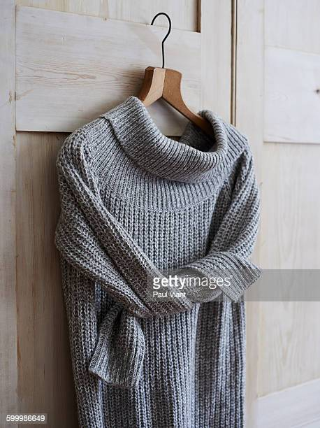 long knitted jumper on wooden coat hanger - sweater stock pictures, royalty-free photos & images